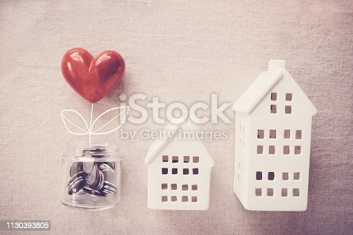 istock A jar of heart tree growing on money coins and model houses, social responsibility, homeless shelter and donation concept 1130393805