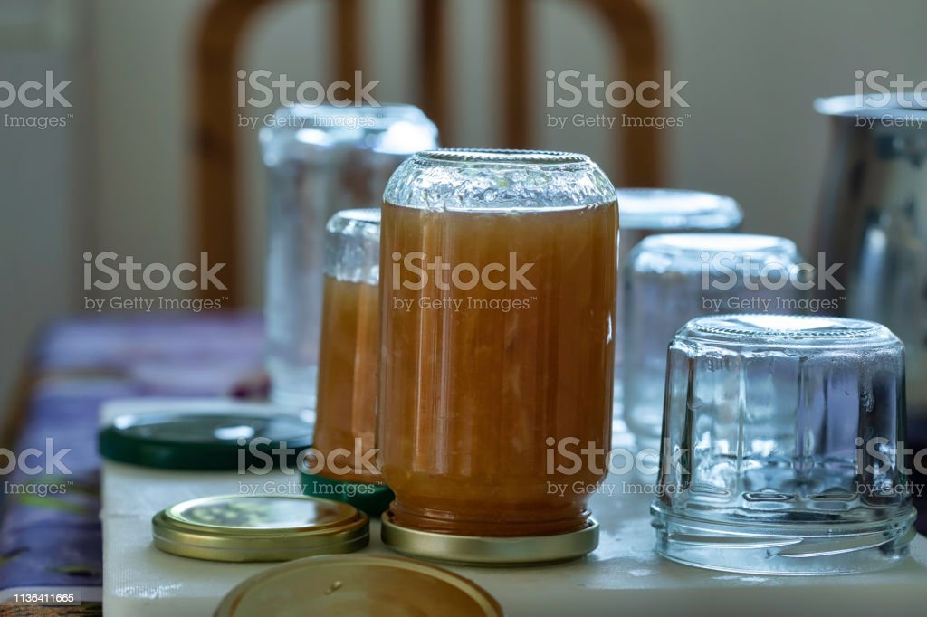 jar of homemade lemon jam: Many jars of jam aligned and placed on a table, some of the pots are filled with lemon jam and put upside down The scene is photographed in a non-professional kitchen, in France on the French Riviera Boiling Stock Photo