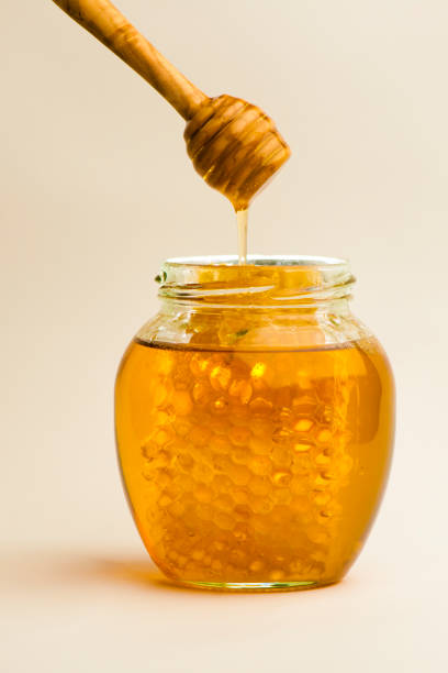 一罐加蜂窩的蜂蜜 - 蜂巢式樣 個照片及圖片檔