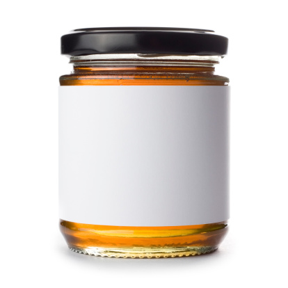 Jar of honey with a blank label isolated on a white background. Ideal for imposing your own artwork onto.