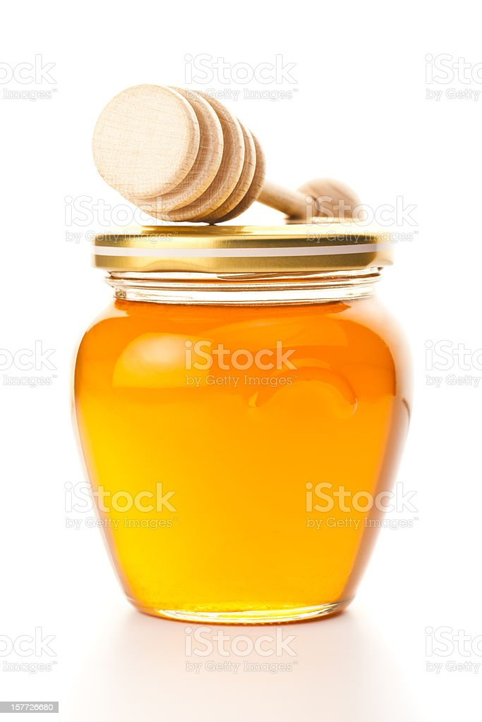 Jar of honey with dipper, isolated on white stock photo