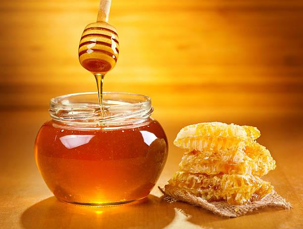 jar of honey with honeycomb stock photo