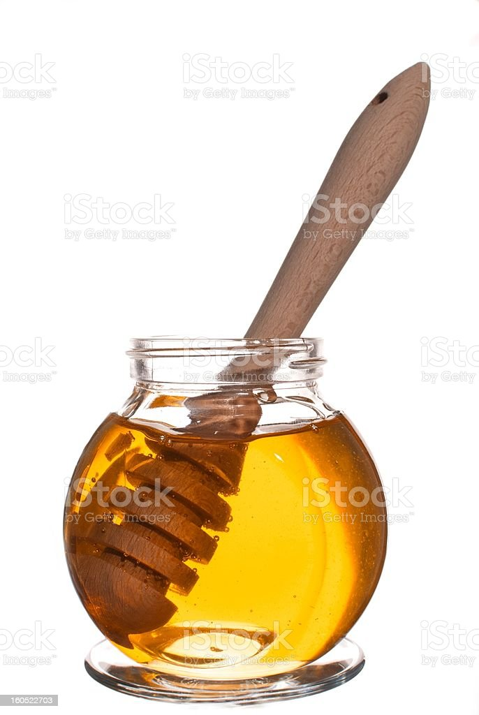 Jar of honey with wooden drizzler isolated on white background royalty-free stock photo