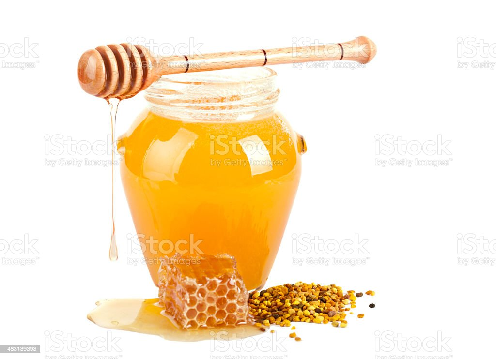 Jar of honey with wooden drizzler stock photo