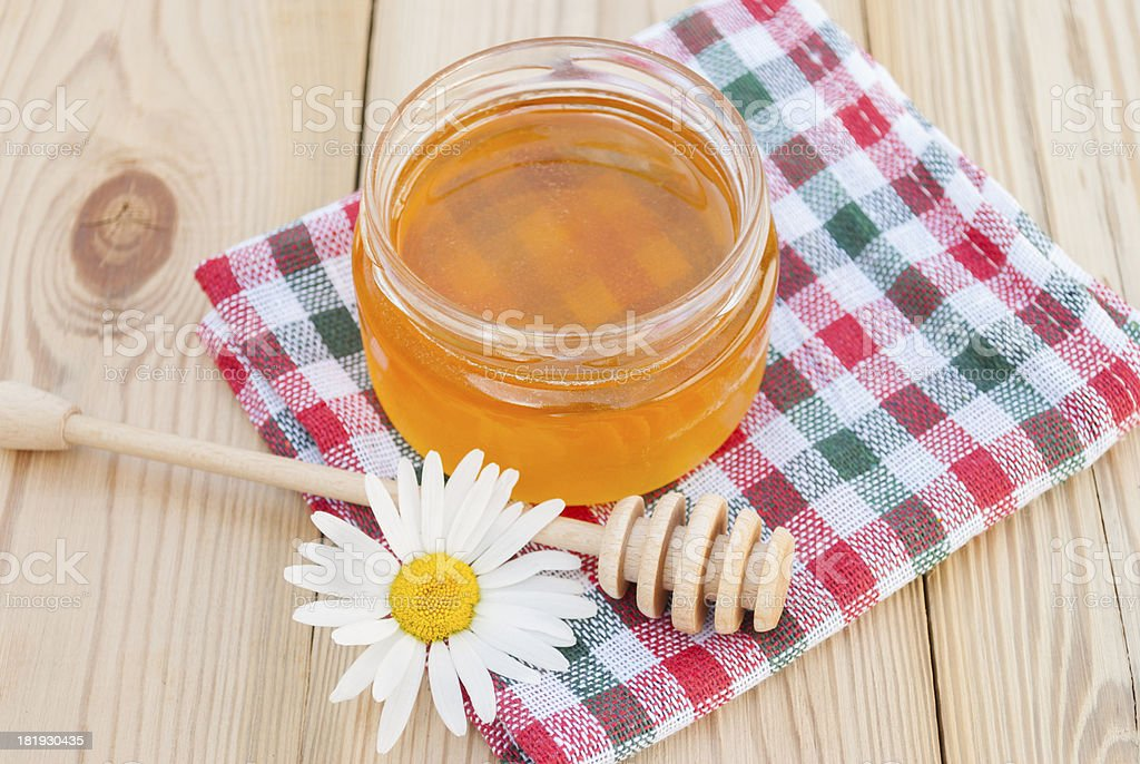 Jar of honey, wooden spoon and chamomile. royalty-free stock photo