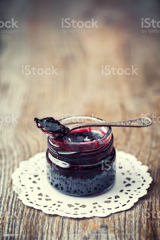 Jar of jam with spoon on old wooden table. stock photo