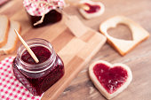 Slice of breads with jam in shape of heart, over brown wooden table