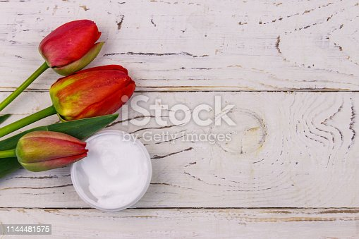 istock Jar of moisturizer cream with red  tulips on white wooden background. Top view, copy space 1144481575