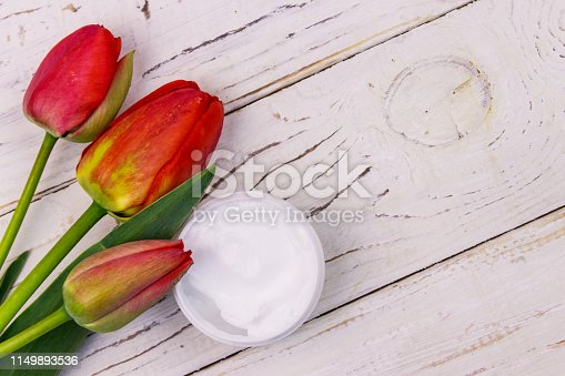 1128479585 istock photo Jar of moisturizer cream with red  tulips on white wooden background. Top view, copy space 1149893536
