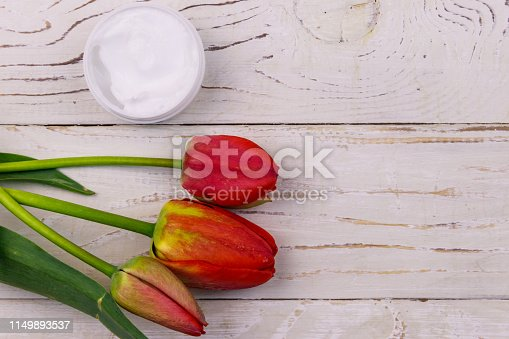 1128479585 istock photo Jar of moisturizer cream with red  tulips on white wooden background. Top view, copy space 1149893537