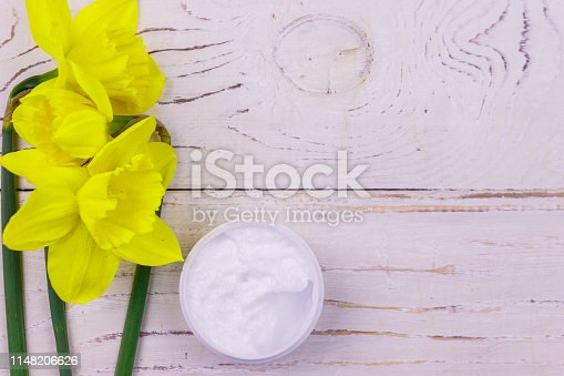 istock Jar of moisturizer cream with yellow daffodils on white wooden background. Top view, copy space 1148206626
