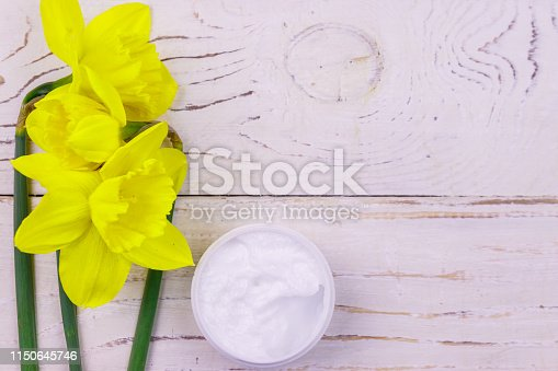 istock Jar of moisturizer cream with yellow daffodils on white wooden background. Top view, copy space 1150645746