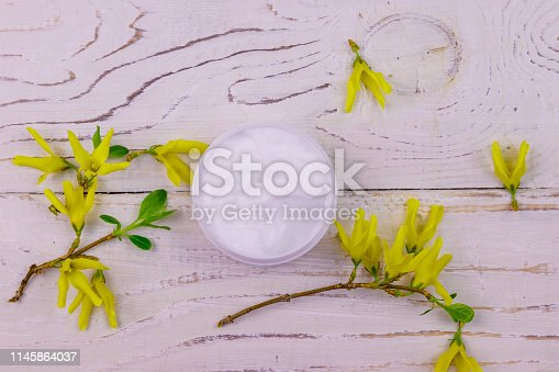 1128479585 istock photo Jar of moisturizer cream with yellow forsythia blossoms on white wooden background. Top view 1145864037