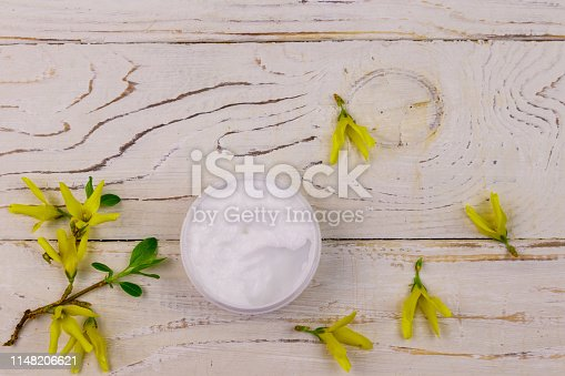 1128479585 istock photo Jar of moisturizer cream with yellow forsythia blossoms on white wooden background. Top view 1148206621