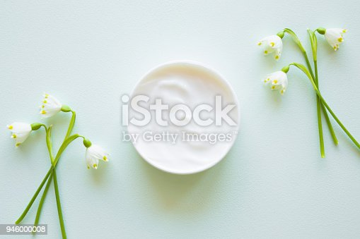 istock Jar of natural herbal cream for women. Beautiful, fresh snowdrop flowers. Care about clean and soft hands, legs and body skin. Top view. 946000008
