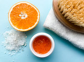istock A jar of orange scrub, a half of orange, body brush on a folded white towel, a pile of large sea salt on a blue background. Spa concept, body cleansing and moisturizing, anti-cellulite 1207967961