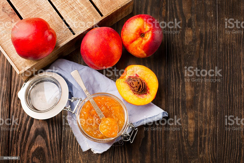 Jar of peach jam with fresh fruits foto royalty-free
