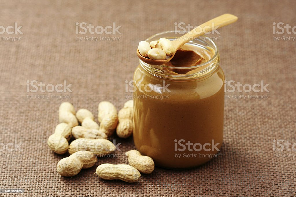 Jar of peanut butter with a spoon and whole peanuts stock photo