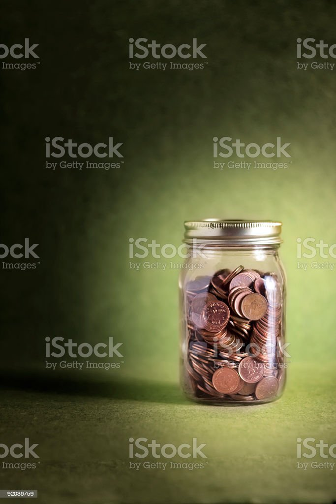 Jar of pennies on green background (Money Series) royalty-free stock photo