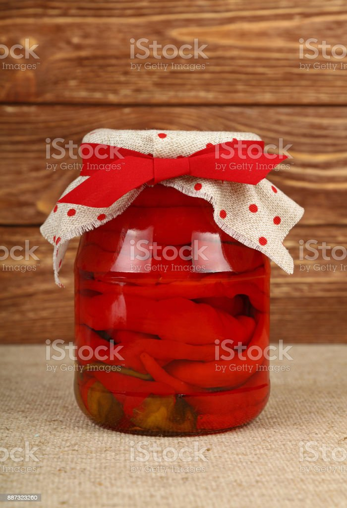 Jar of pickled red hot chili peppers on table stock photo