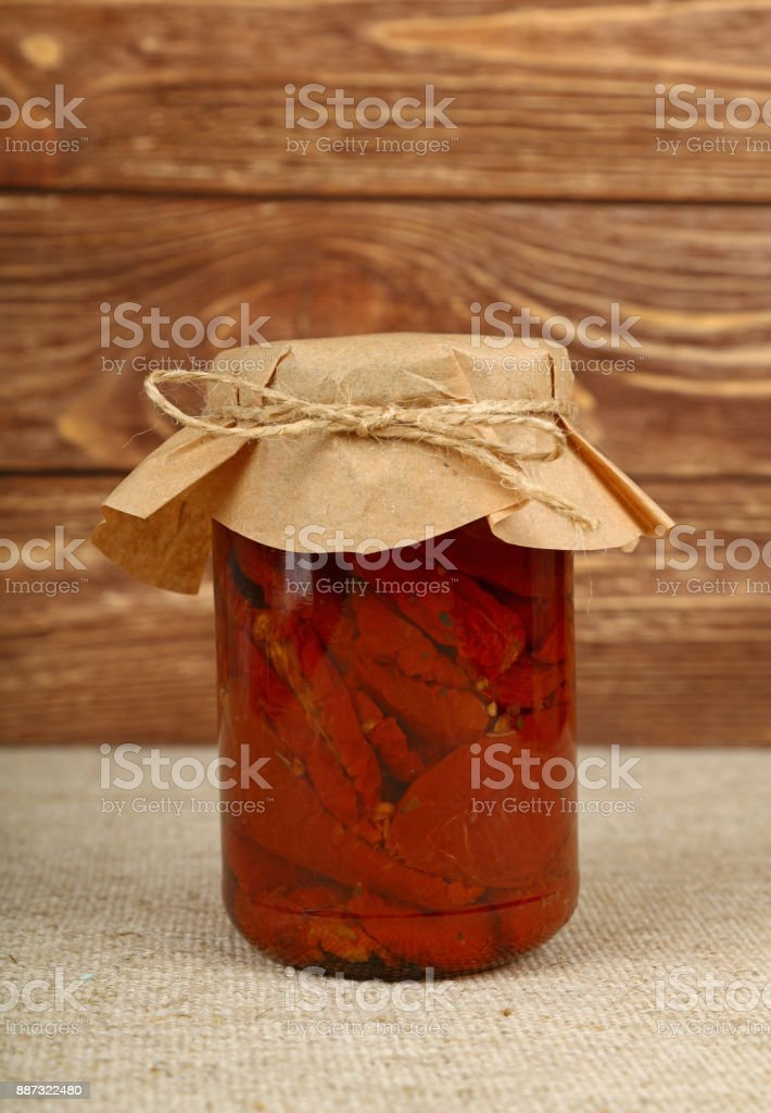 Jar of pickled sundried tomatoes on table stock photo