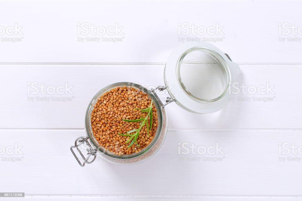 jar of raw buckwheat stock photo