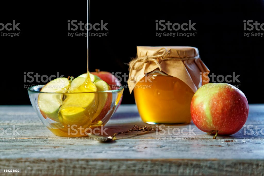 Jar of rustic honey and and apples on wooden table. Traditional celebration food for the Jewish New Year. Concept Rosh Hashana stock photo