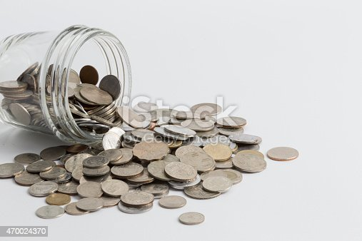 Jar spilling coins of multiple currencies isolated against a white background