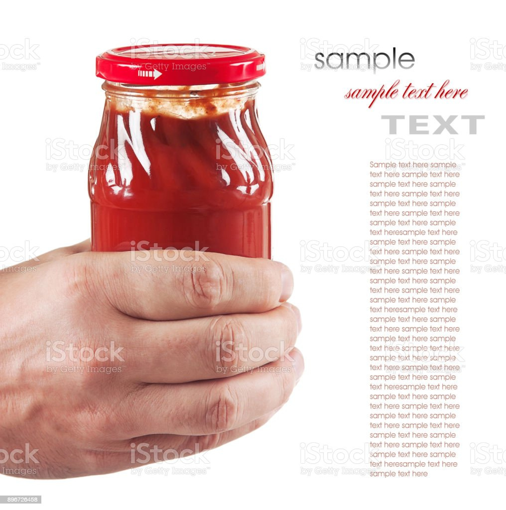 jar tomato paste in hand stock photo
