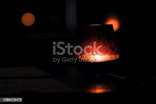 A jar with a candle on a table