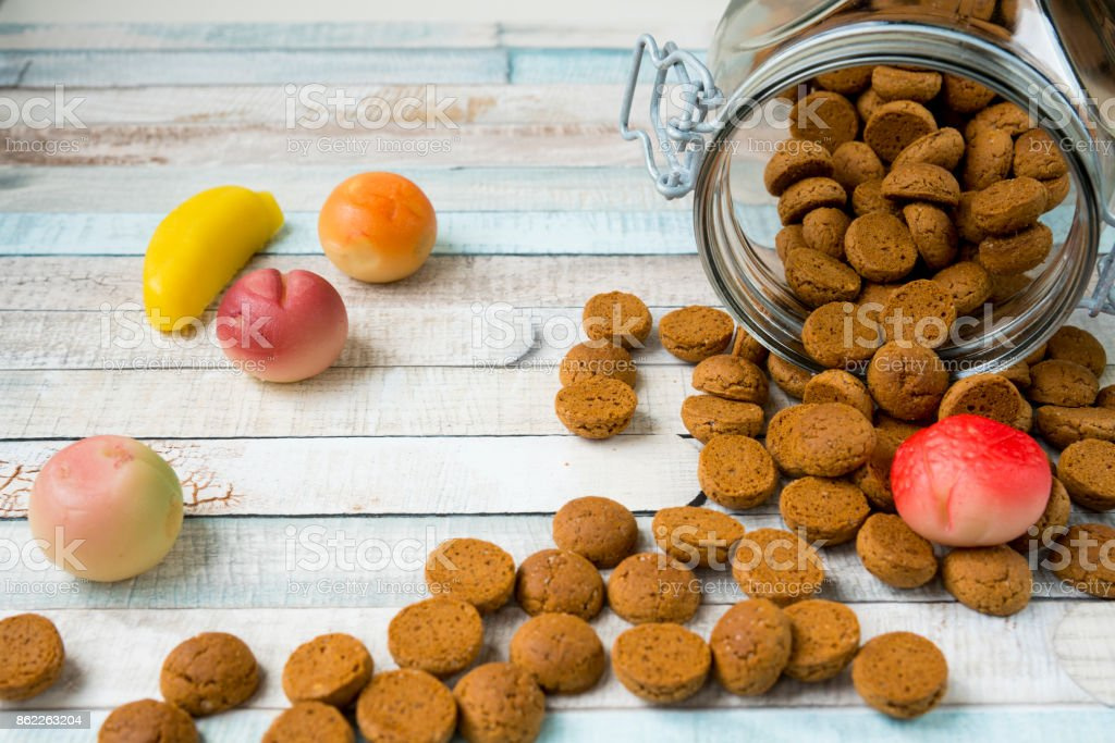 jar with Dutch kruidnoten, spiced cookies, with fruit marzipan and present. celebrating Dutch event Sinterklaas stock photo