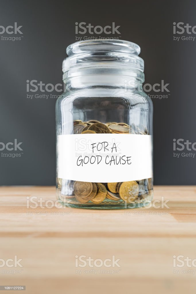 Jar with golden coins on natural wooden background. stock photo