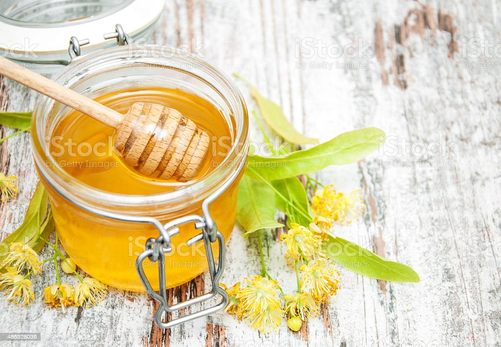 Jar with honey Jar with honey and linden flowers on a wooden background 2015 Stock Photo