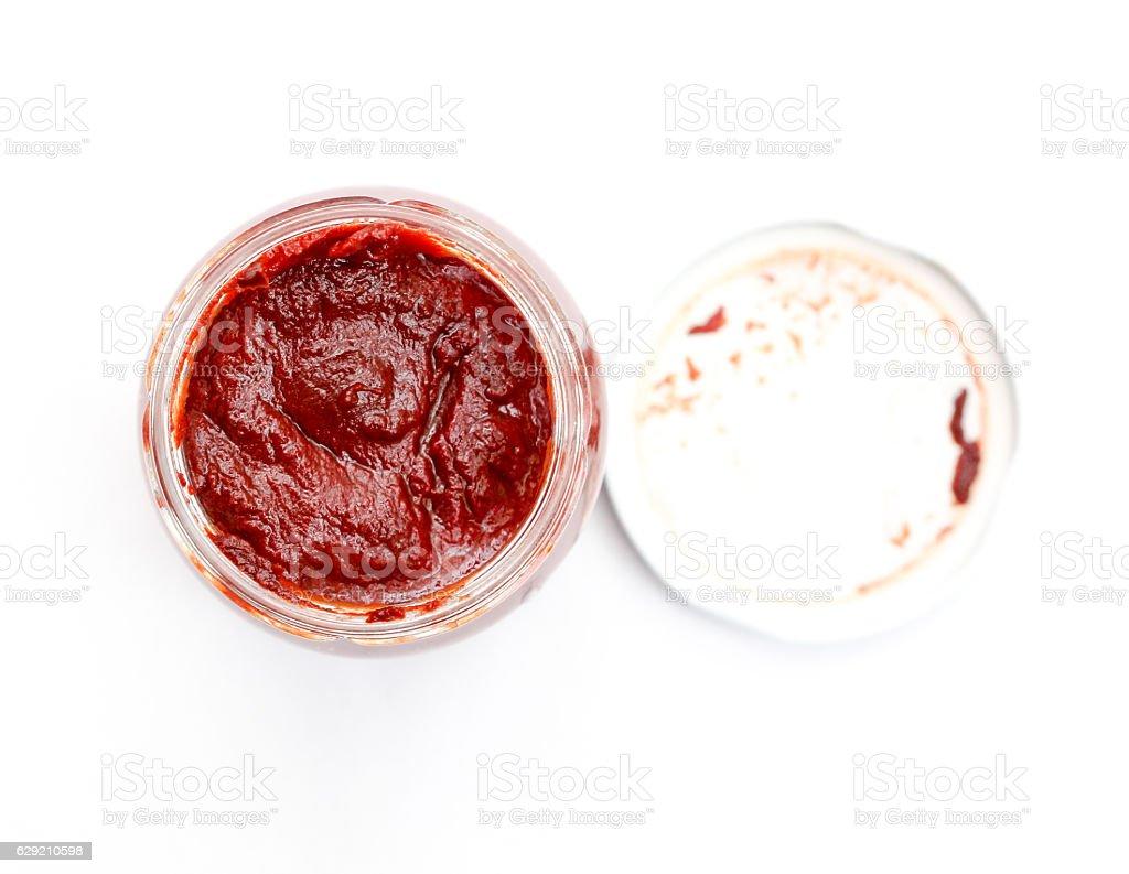 Jar with jomato paste , top view on white. stock photo