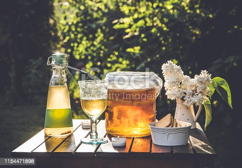 Jar with kombucha drink and tea mushroom in and served in glass outdoors in sunny summer evening, garden, cookies in bowl and white lilac flower in jar shape vase.