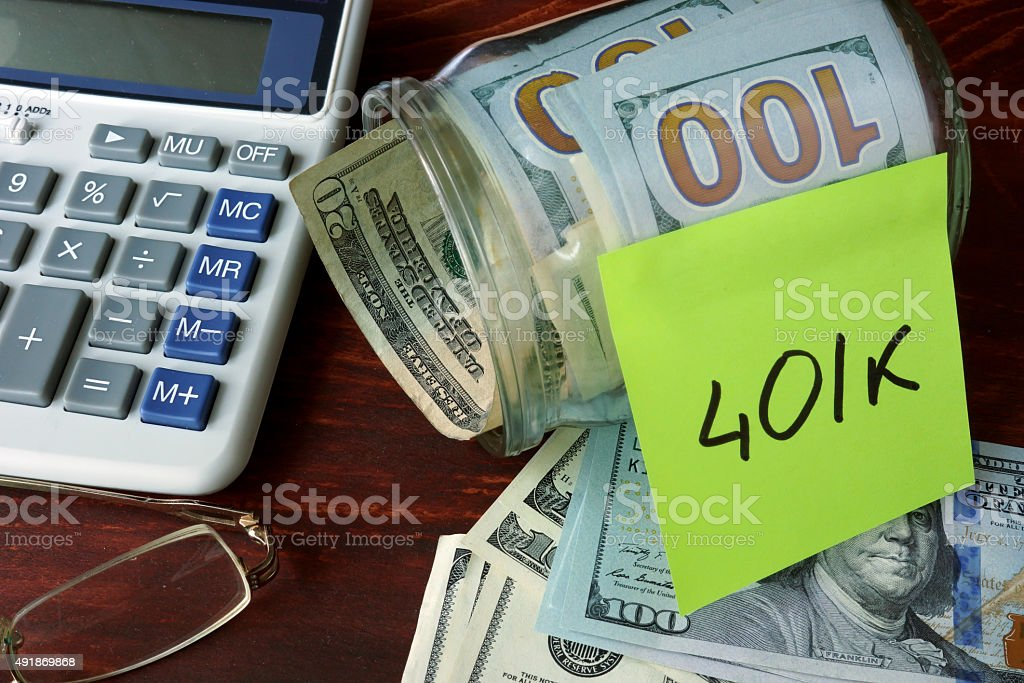 Jar with label 401k and money on the table. stock photo