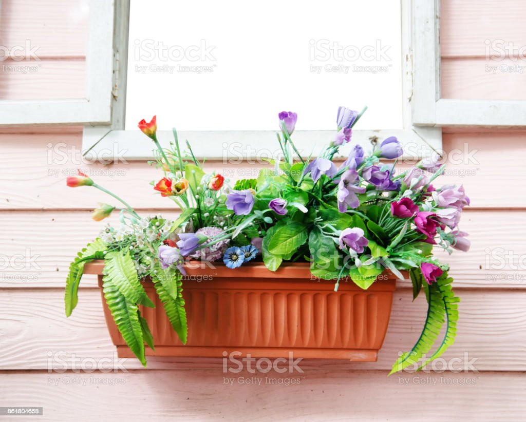 jardiniere on window with pink wood background  and plastic flower stock photo