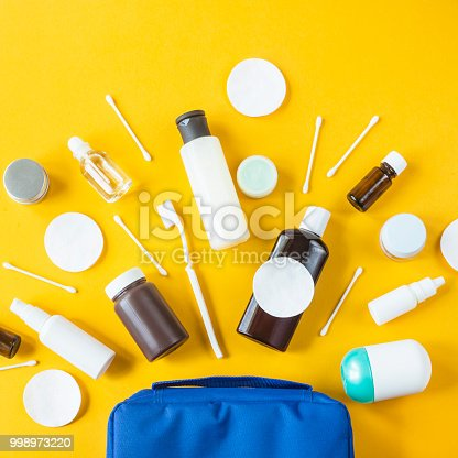 Jars and containers with cosmetics and cotton buds with disks from a blue cosmetic bag on a yellow background. Top view, flat lay