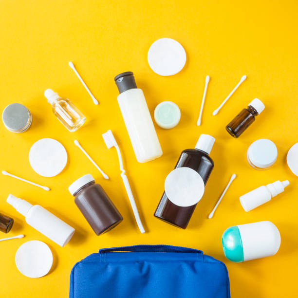 jars and containers with cosmetics and cotton buds with disks from a blue cosmetic bag on a yellow background. top view, flat lay - przybory toaletowe zdjęcia i obrazy z banku zdjęć