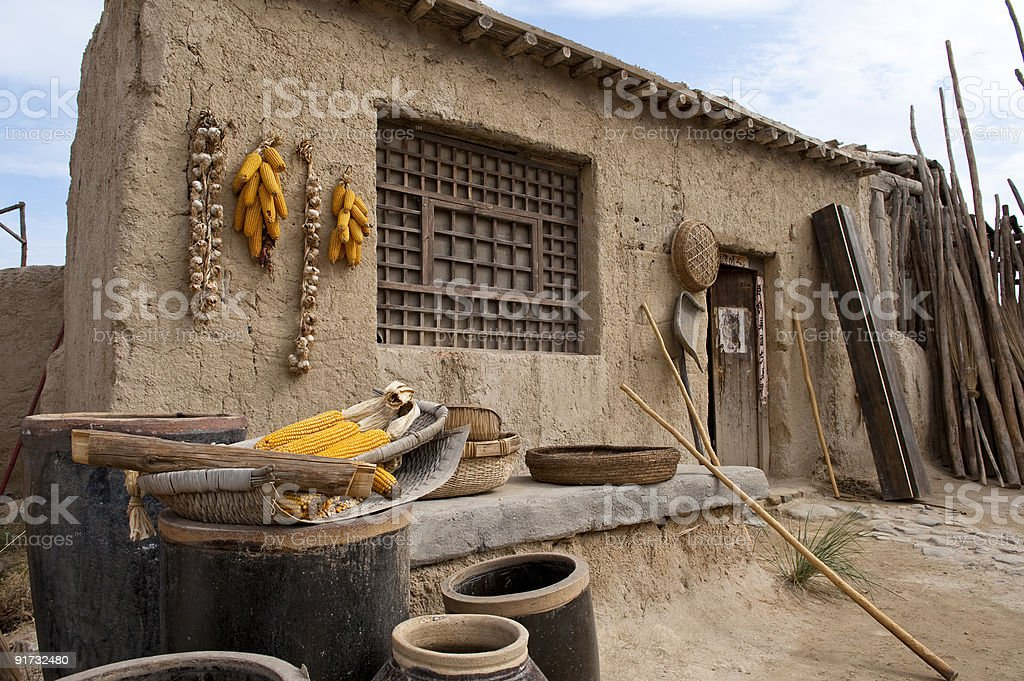 Jars and tools in front of clay house stock photo