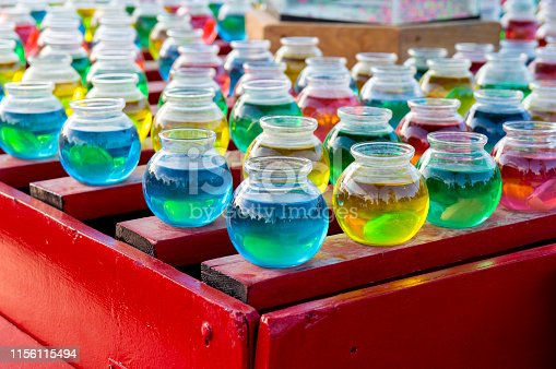 These colorful glass jars are filled with different colored liquids.  They were part of a carnival booth in which a contestant tried to get a pingpong ball to land inside one of the jars.  Winners got to take home a goldfish in a plastic bag.