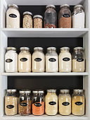 Jars of Flours and grains on white shelves in pantry