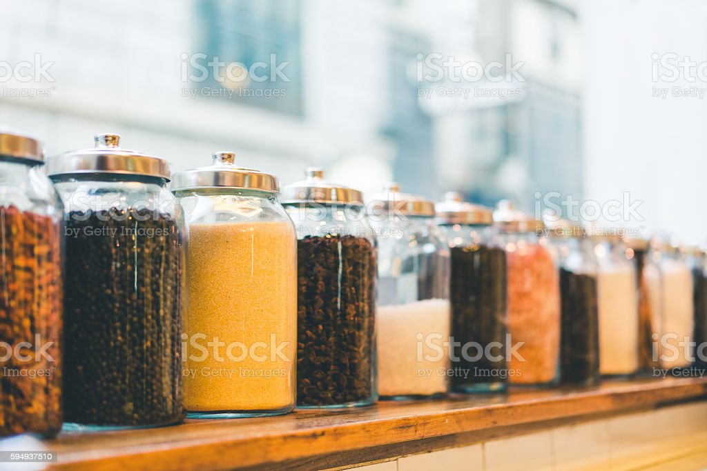 Jars of coffee beans, sugar, and ingredients in vintage tone stock photo
