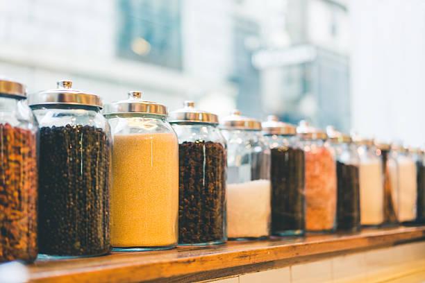 jars of coffee beans, sugar, and ingredients in vintage tone - teeladen stock-fotos und bilder