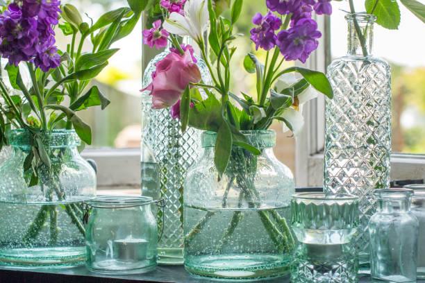 gläser von blumen auf der fensterbank - vase glas stock-fotos und bilder
