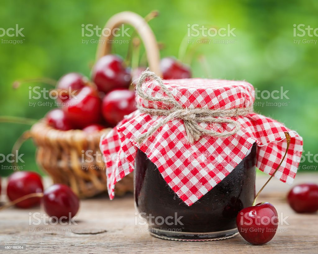 Jars of jam and basket with cherry stock photo