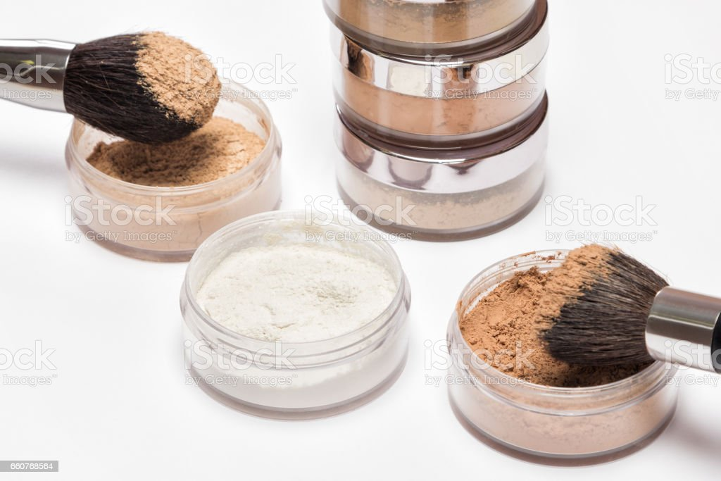 Jars of loose cosmetic powder with makeup brushes stock photo