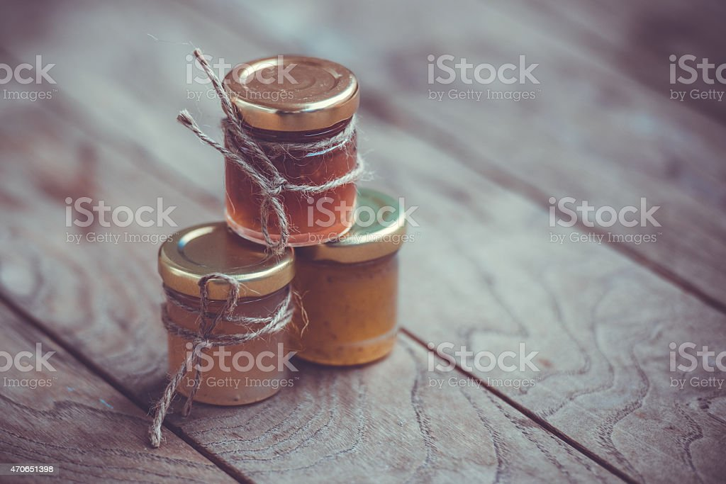 Jars of marmalade wrapped in twine on a wooden table stock photo