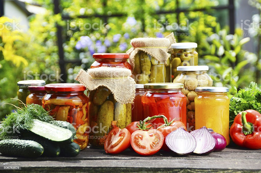 Jars of pickled vegetables in the garden. Marinated food stock photo
