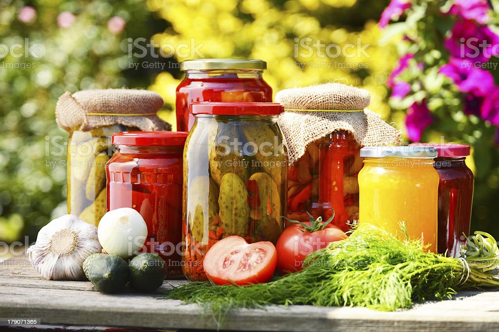 Jars of pickled vegetables in the garden stock photo